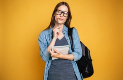 Cute woman writes some notes in notepad. Young blonde student girl is thoughtful with pencil in hand and with backpack on yellow background