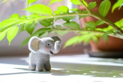Cute woolly toy elephant under green leaves on a sunny day. Dry felting.