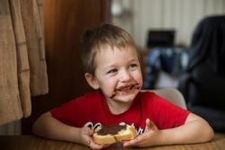 Cute 5 y.o. boy eating  chocolate cream and his face and hands smeared with chocolate cream.