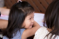 Cute 3 year old Asian girl is sitting chatting with friend beside her and sending sweet smile to friend or sister.Both sitting they began to study art and water painting on large white paper.