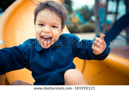 Cute 3 year old boy excitedly plays on a yellow playground slide on a cool cloudy day