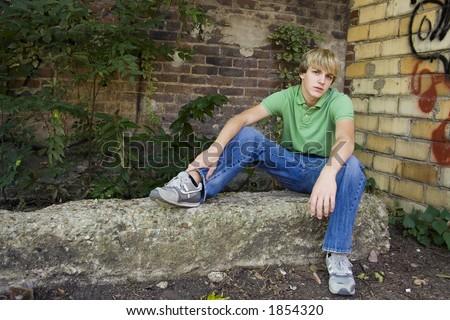 Cute 15 year old boy sitting outside by brick wall.