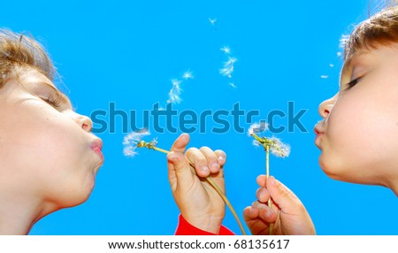 cute 4 year old girls blowing dandelion seeds away