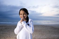 Cute 9 year old Hispanic girl smiling on beach at dawn