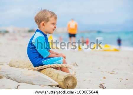 Cute 2 years old boy looking at kiting on tropical beach