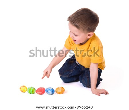 Cute 3-years old boy playing with Easter eggs. Isolated on white.