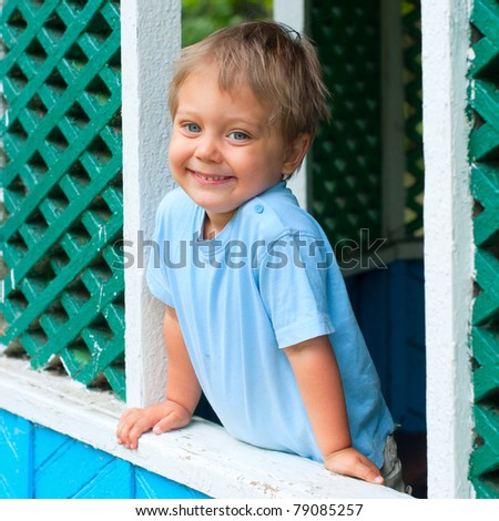 Cute 2 years old boy sitting in the summer house in park
