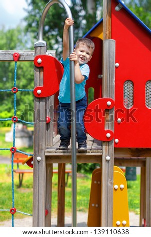 Cute 3 years old boy smiling on the top of playground