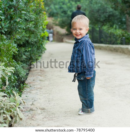 Cute 2 years old boy standing on the footpath in the park - stock photo