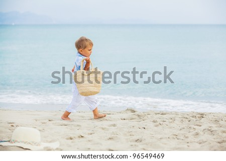 Cute 2 years old boy with beach bag runing on tropical beach