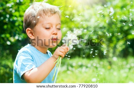 Cute 2 years old boy with dandelion outdoors at sunny summer day