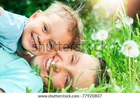 Cute 2 years old boy with mother lying in the grass at sunny summer day