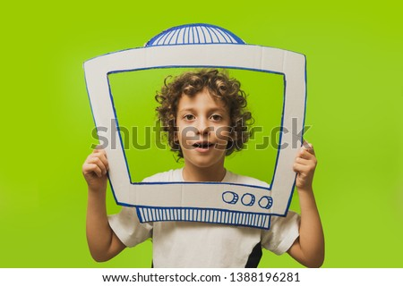 Cute 6-8 years old kid talking inside a cutout diy television. Youtuber kids concept.