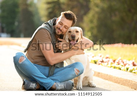 Cute yellow labrador retriever with owner outdoors #1114912505