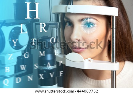 Cute young adult brunette woman at the future clinic checks her vision. Virtual sensors for checking vision. Ophthalmology. Future medicine and health concept.