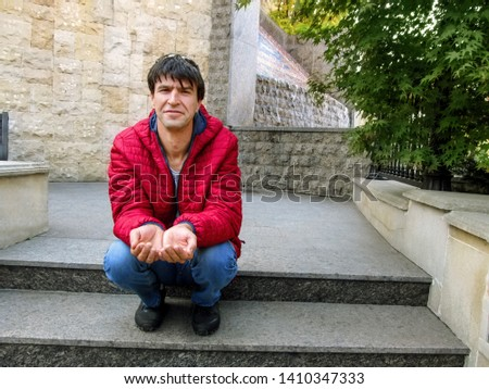 Cute young adult guy stretches his two open up empty palms, smiling, squatting. Dark-haired man is fooling around, imitating the begging movement or ask gesture, in Heydar Aliyev Park in Kiev, Ukraine