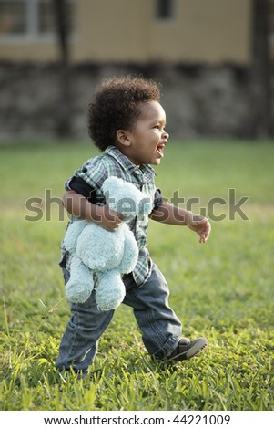 Cute young African American toddler walking on a field of grass