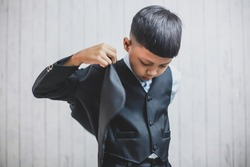 Cute young asian boy putting on his business suit jacket. Studio shot. Fashionable look. Small businessman.