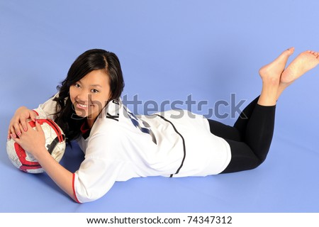 Cute young Asian female soccer player or fan laying down on her stomach against a blue background and cradling a soccer ball