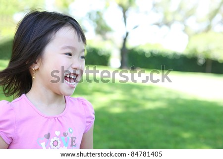 Cute young asian girl in the park having fun