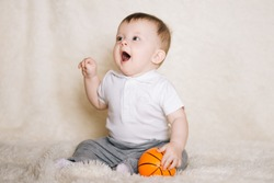 Cute young baby sitting on the floor at home and playing with a basketball, sports, healthy and active lifestyle