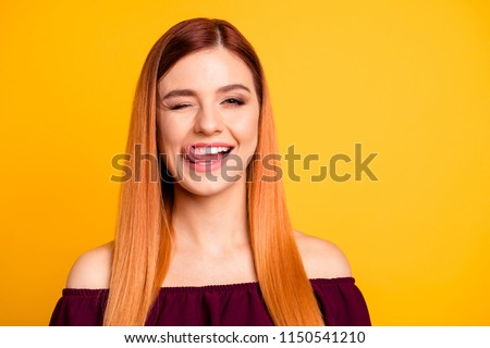 Cute young beautiful girl smiling and winking showing tongue looking at camera isolated on yellow background