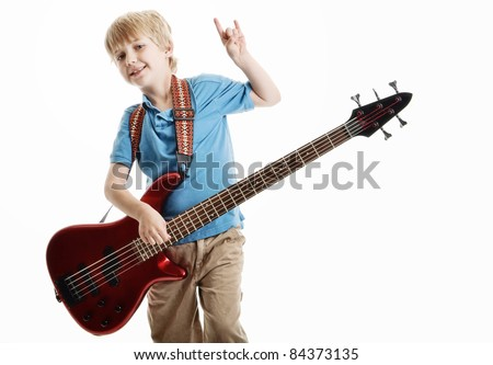 Cute young blond haired boy playing an electric guitar against a white background - stock photo