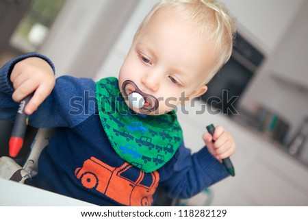 Cute young blonde baby with a dummy in his mouth sittong at a table with an engrossed expression drawing with a wax crayon