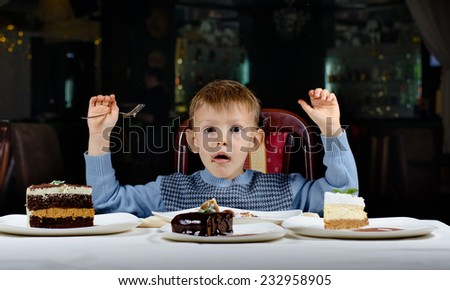 Cute young boy celebrating his birthday with a line up of different cake in front of him pulling a comic face as he tries to make up his mind where to begin eating