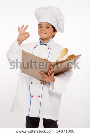 Cute young boy dressed as a chef consulting a book