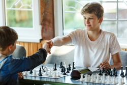 cute, young boy in white t-shirt shake hand to his rival before chess game. chess Training, lesson, tournament concept