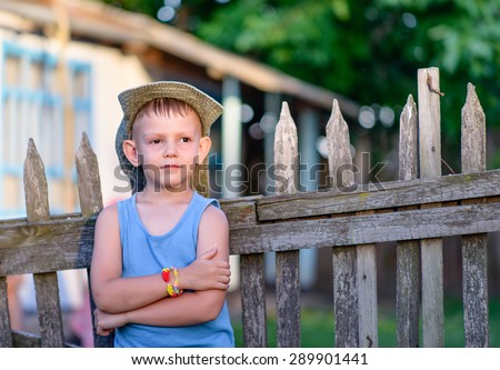Cute Young Boy Leaning Against the Wooden Fence with Arms Crossed Over his Stomach, Showing a Pensive Facial Expression.