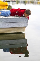 Cute young boy looking into the water off a dock with reflection