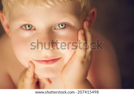 Cute young boy looking up with blond hair and hands close to the face