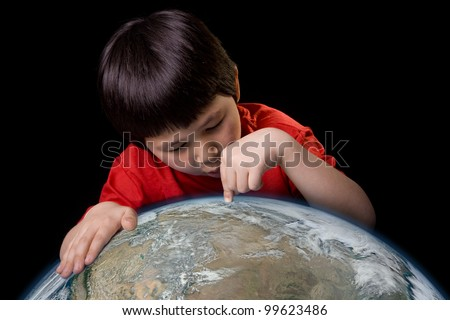 Cute young boy pointing to a spot on planet earth with space background. Elements of this image furnished by NASA.