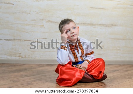 Cute young boy sitting on a wooden floor in a colorful dance or pantomime costume scratching his head and thinking with a puzzled expression