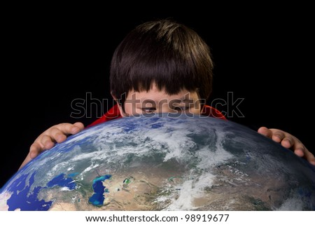 Cute young boy taking a close up look at a spot on planet earth with space background. Elements of this image furnished by NASA.