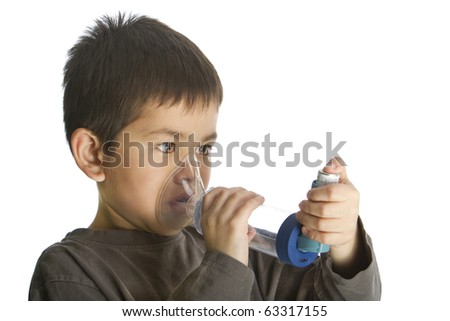 Cute young boy using his asthma inhaler with and aero chamber isolated on white background