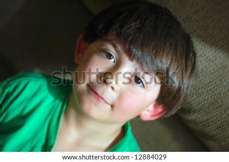 Cute young boy wearing a green shirt looking at the camera.