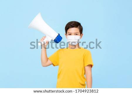 Cute young boy wearing medical mask holding megaphone isolated on light blue background