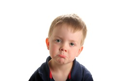 Cute young boy with blond hair and green eyes with sad or pouting face, isolated on white