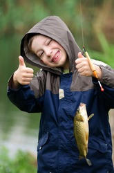 Cute young boy with great smile holding carp and show a thumb up