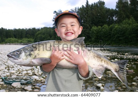 Cute young boy with great smile holding large salmon out fishing on a river