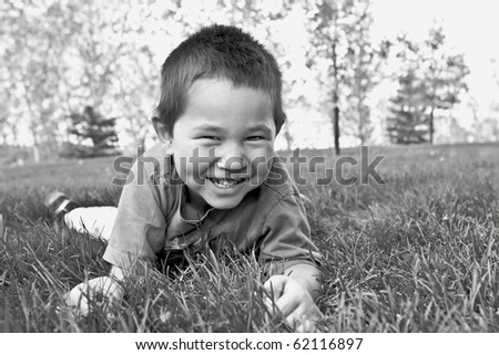 Cute young boy with great smile laying in the grass - Black and White