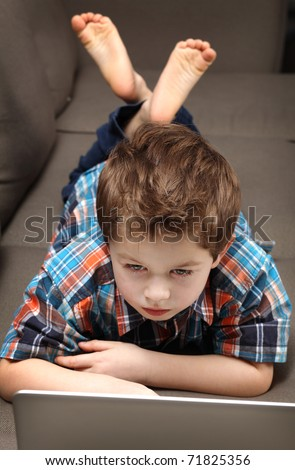 cute young boy with laptop on a couch
