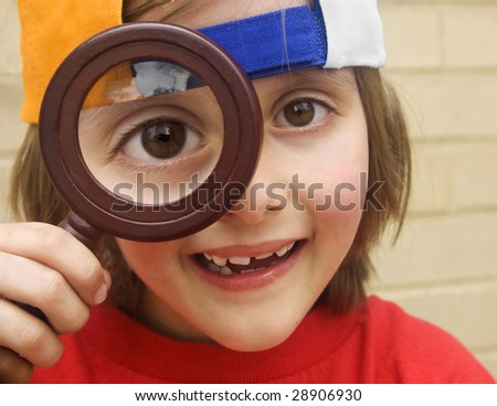 cute young boy with magnifying glass