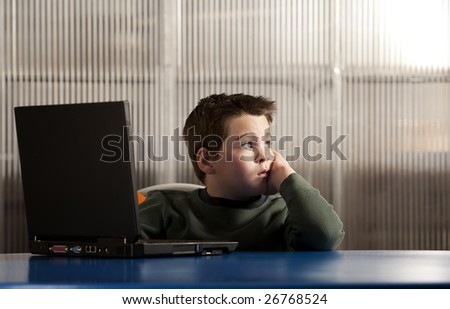 Cute young boy working on a laptop computer