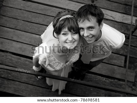 Cute young bride and groom looking up