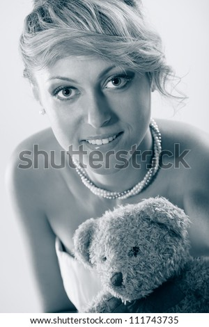 Cute young bride holding teddy bear