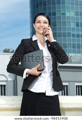 Cute young business lady talking mobile phone and holding laptop in hand against modern office building